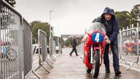 Man pushes bike in the rain