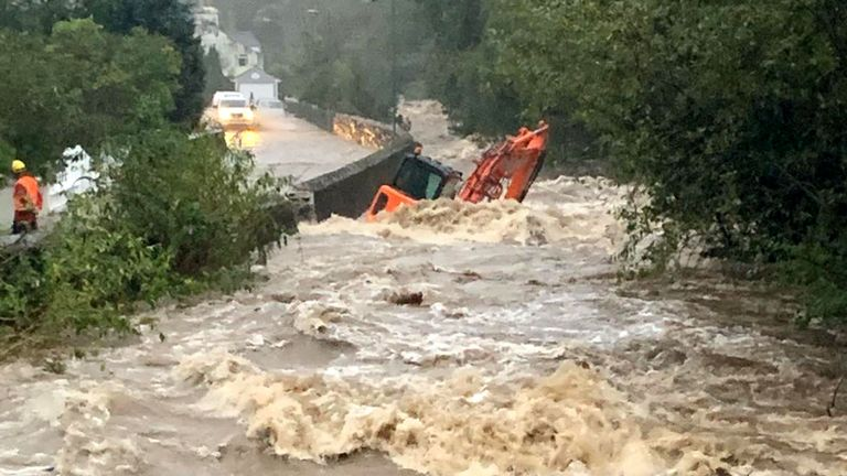 A construction vehicle appeared to have been knocked over by floodwater in Laxey