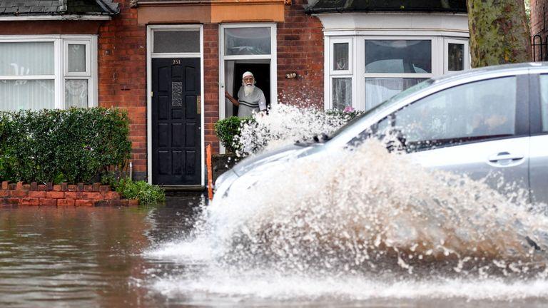 A car drives down a flooded road in Alum Road, Birmingham