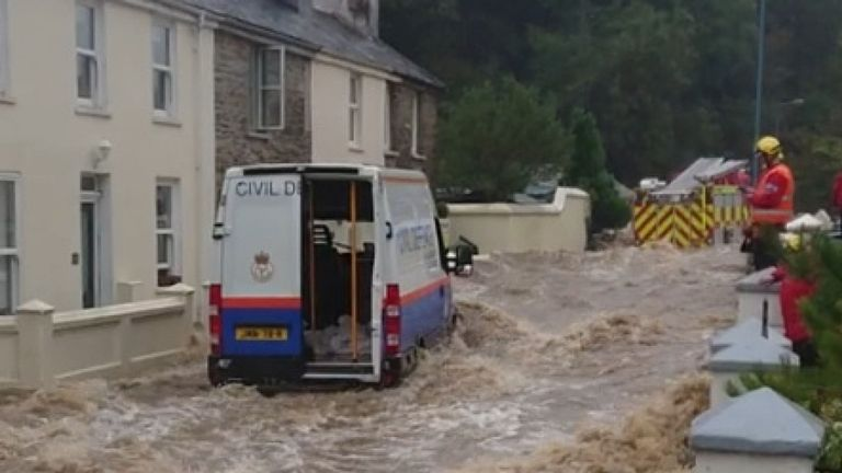 A civil defence vehicle and a fire engine can both be seen on a flooded street in Laxey