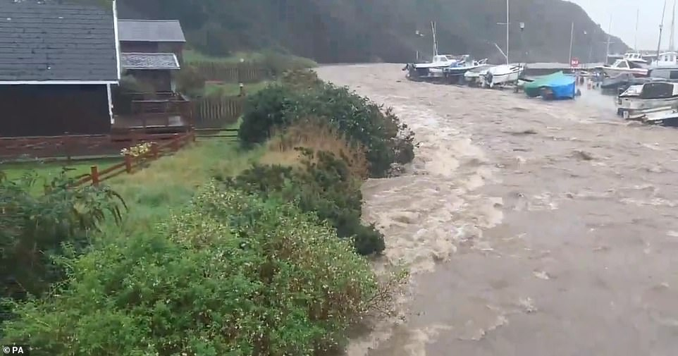 Flash flooding this morning at Laxey Harbour on the Isle of Man as residents become trapped in their homes today