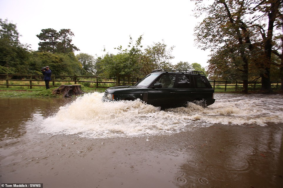 A Land Rover drives through deep flood water which has deluged the village of Colston Bassett in Nottinghamshire today