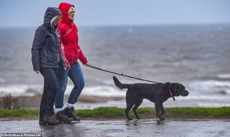 People brave the weather conditions and try to ignore the heavy rainfall as they stroll along Whitley Bay seafront today