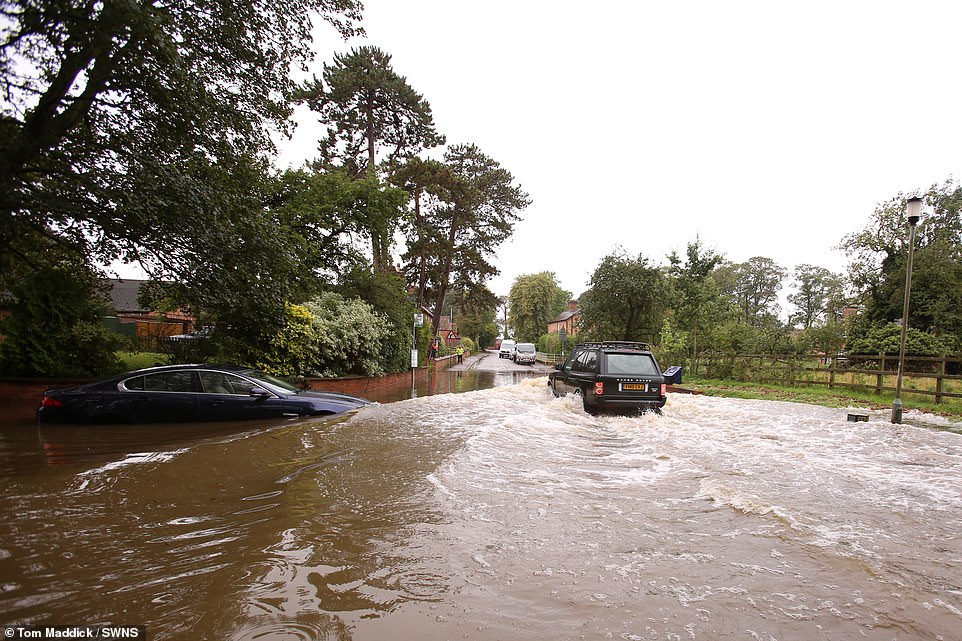 A Land Rover drives through deep flood water which has affected the Nottinghamshire village of Colston Bassett today