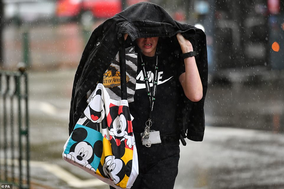 Morning commuters make their way through a heavy rain shower in Birmingham today as they take cover under coats