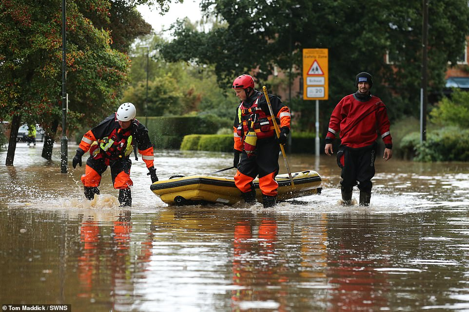 Fire rescue teams wade through floodwater this morning after heavy rain in the village of Cossington, Leicestershire