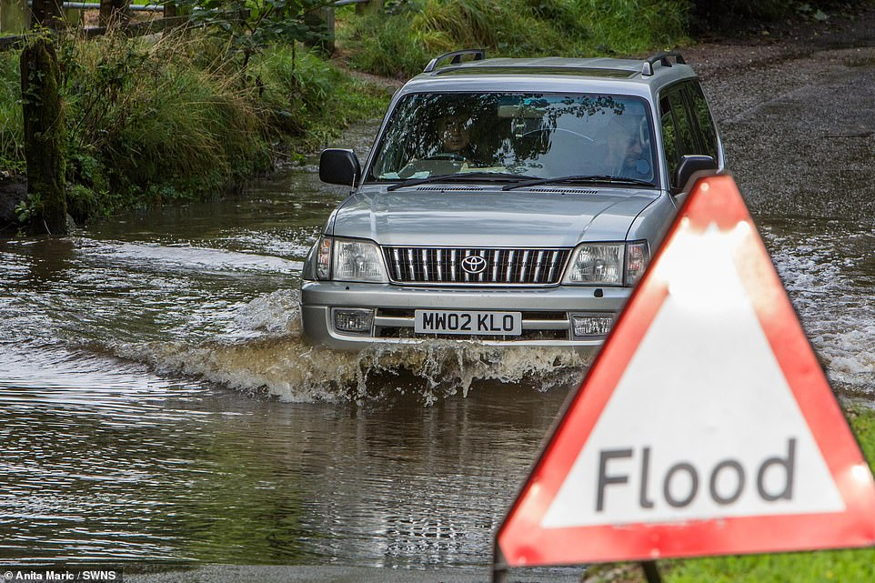 A motorist drives his car through floodwater in Birmingham today as much of the UK is battered by severe weather