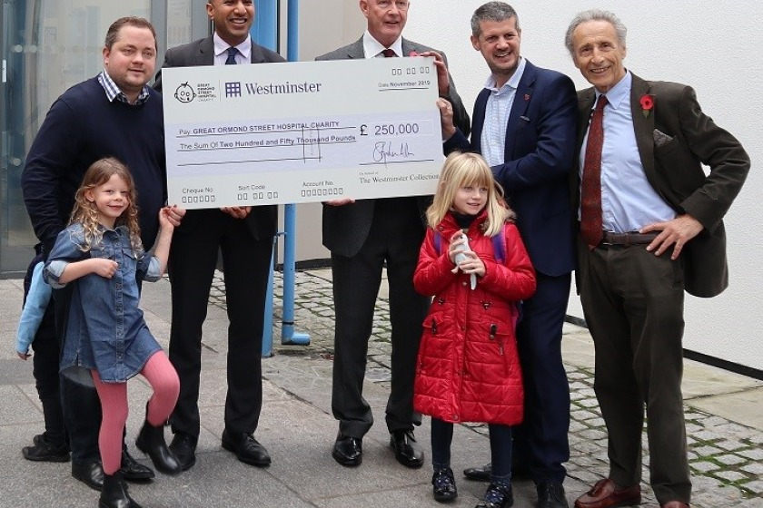 Bill Henderson MLC and his daughter Sophia, in red coat, are pictured at Great Ormond Street Hospital on Thursday with, from left, Tower Mint director Elliot Dawson and his daughter Olivia, Director of Corporate Partnerships at GOSH Amit Aggarwal, Ian Glen from Westminster Collections and Tower Mint chairman Raphael Maklouf
